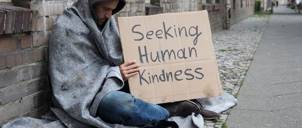 Homeless man holding Seeking Human Kindness cardboard sign